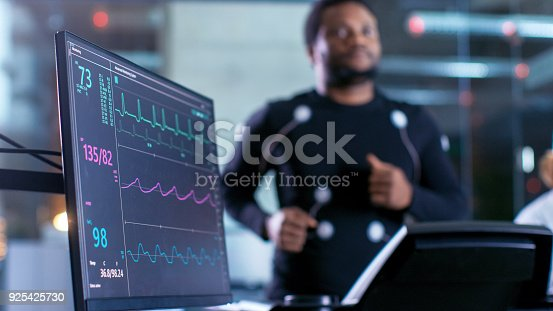 istock Close-up Shot of a Monitor With EKG Data. Male Athlete Runs on a Treadmill with Electrodes Attached to His Body while Sport Scientist Holds Tablet and Supervises EKG Status in the Background. 925425730