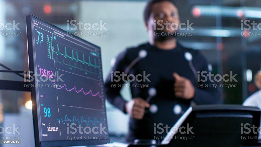 Toma de primer plano de un Monitor con datos de electrocardiograma. Atleta Masculino corre en una caminadora con electrodos conectados a su cuerpo mientras que deporte científico tiene tableta y supervisa estado de electrocardiograma en el fondo. - foto de stock