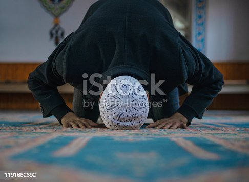 Close-up shot of a Muslim young man worshiping in a mosque. Horizontal composition.
