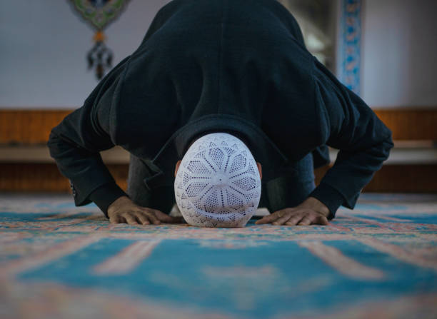 Close-up shot of a Muslim young man worshiping in a mosque Close-up shot of a Muslim young man worshiping in a mosque. Horizontal composition. religious celebration stock pictures, royalty-free photos & images