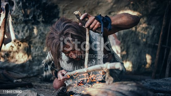 841481956 istock photo Close-up Shot of a Primeval Caveman Wearing Animal Skin Trying to make Fire with Bow Drill Method. Neanderthal Kindle First Man-Made fire in the Human Civilization History. Making Fire for Cooking. 1194512880
