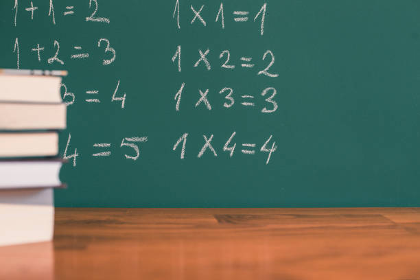 Close-up shot of a school board with numbers on it and books on the desk stock photo