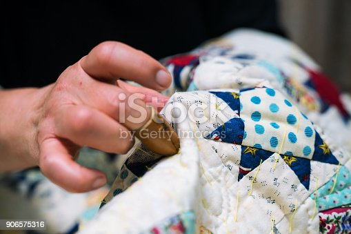 A close-up shot of a senior woman sewing and making crafts in her home