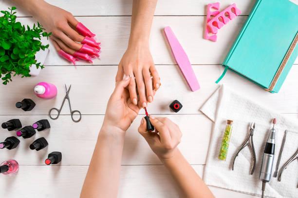 closeup aufnahme einer frau in einem nagelstudio erhalten eine maniküre von einer kosmetikerin mit nagelfeile. frau immer nagel maniküre - nailstudio stock-fotos und bilder