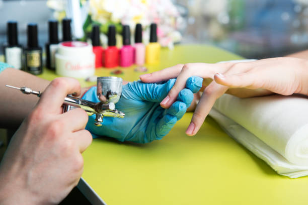 Closeup shot of a woman in a nail salon receiving a manicure by a beautician with nail file. Woman getting nail manicure. Beautician file nails to a customer stock photo