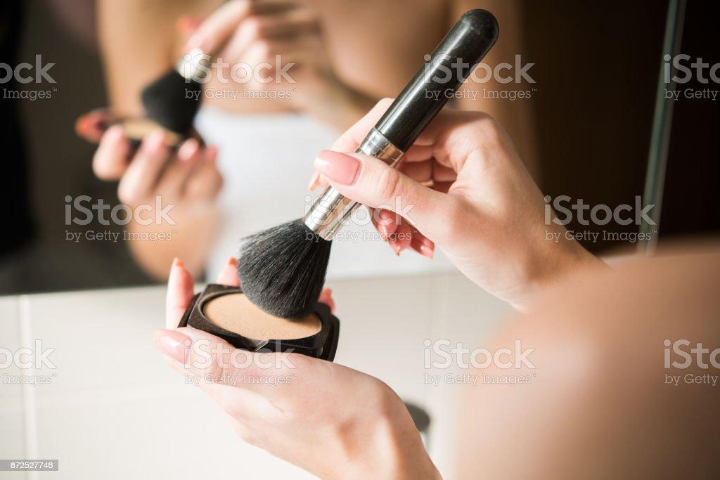 Close-up shot of a woman putting powder on a make-up brush stock photo