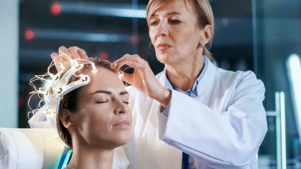Close-up shot of a Woman Wearing Brainwave Scanning Headset Sits in a Chair while Scientist Adjusts the Device. In the Modern Brain Study Laboratory Monitors Show EEG Reading and Brain Model. stock photo