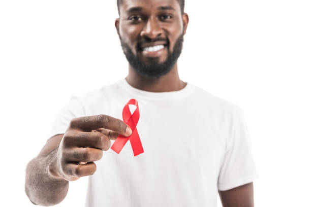 close-up shot of african american man in blank white t-shirt with aids awareness red ribbon looking at camera isolated on white close-up shot of african american man in blank white t-shirt with aids awareness red ribbon looking at camera isolated on white hiv stock pictures, royalty-free photos & images