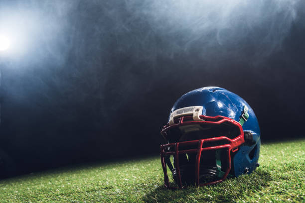 close-up shot of american football helmet on green grass with white smoke above close-up shot of american football helmet on green grass with white smoke above football helmet stock pictures, royalty-free photos & images