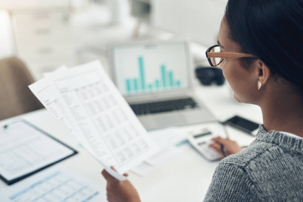 Closeup shot of an unrecognisable businesswoman calculating finances in an office stock photo