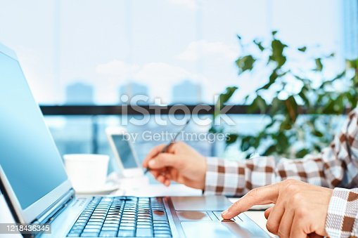 624546230 istock photo Close-up shot of an unrecognizable man taking notes while using a laptop 1218436345
