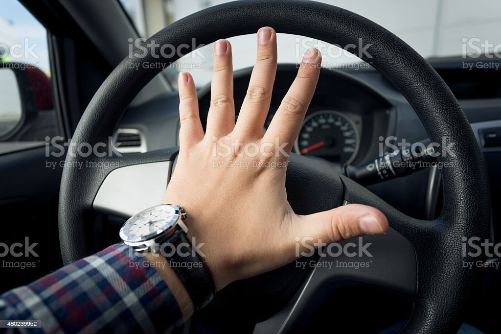 Closeup shot of angry driver honking in traffic stock photo