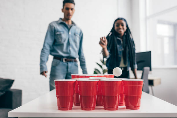 close-up shot van bal vliegen in plastic beker in bier pong spel en jonge multiculturele paar permanent achter - beirut stockfoto's en -beelden