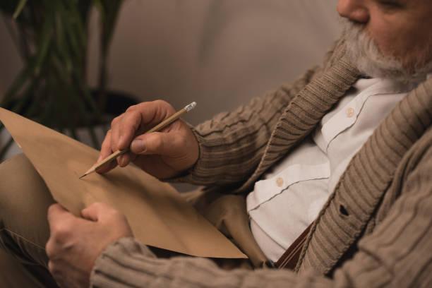 close-up erschossen senior bärtigen brief schreiben - gedichte zum ruhestand stock-fotos und bilder
