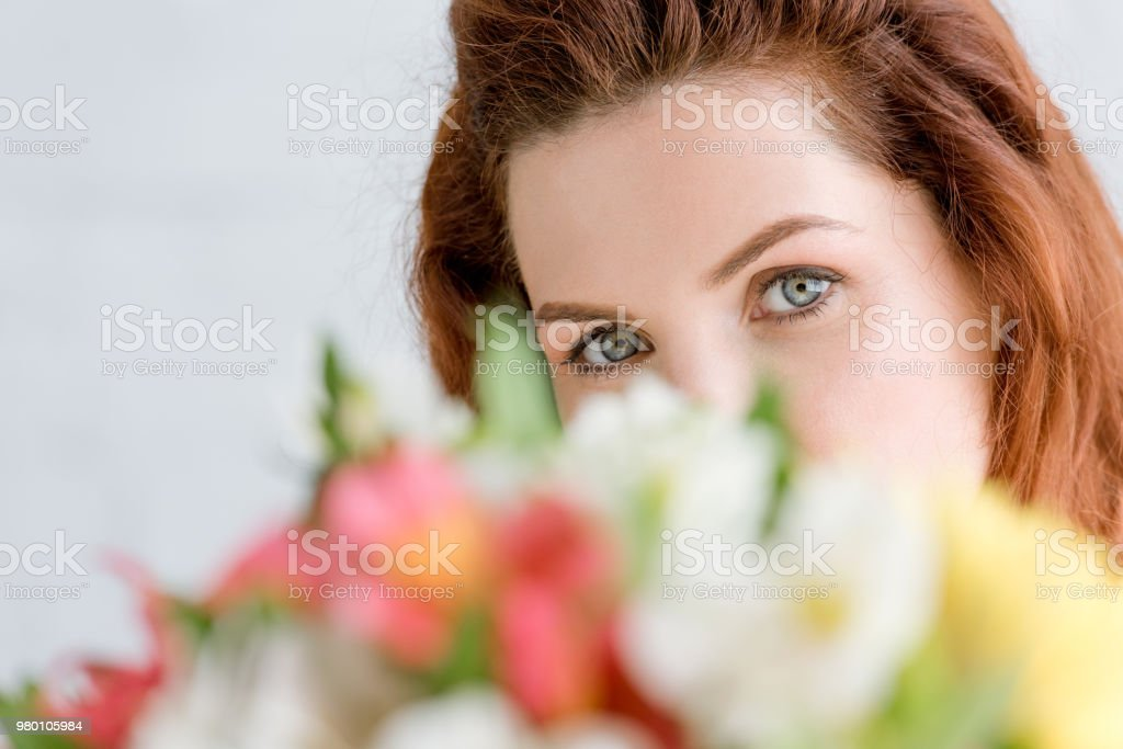 close-up shot of beautiful young woman peeking behind flowers bouquet and looking at camera stock photo