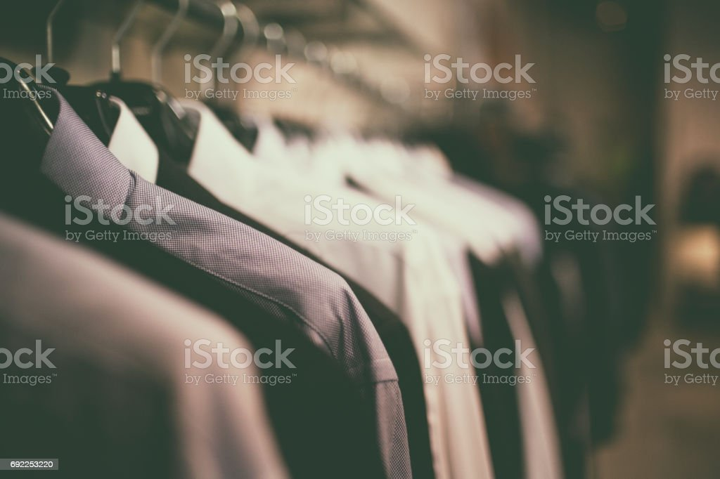 Close-up shot of blue blouses with coathangers on a clothes rack. stock photo