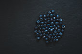Small fresh berries on black stone textured background - Blueberries as source of vitamins and nutrients on a healthy diet