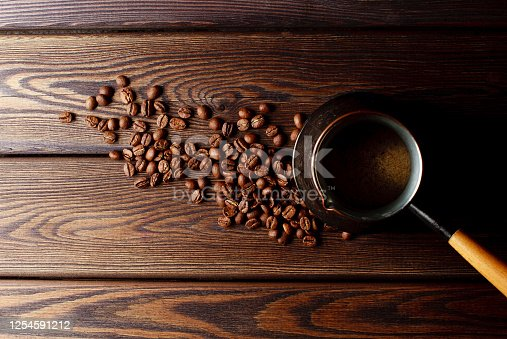 close-up shot of cezve with coffee beans on rustic wooden table top view in San Salvador, San Salvador Department, El Salvador