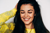 istock Closeup shot of charming brunette young woman wears yellow jumper, touching her hair, smiling with closed eyes enjoying the positive feelings, isolated over white background. 1223943742