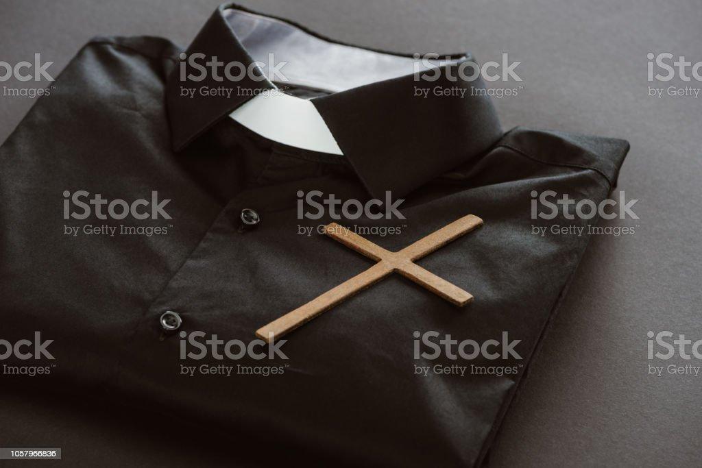 close-up de camisa clerical com cruz na superfície cinza - foto de acervo