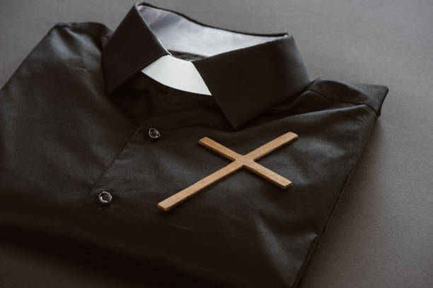 close-up shot of clerical shirt with cross on grey surface close-up shot of clerical shirt with cross on grey surface clergy stock pictures, royalty-free photos & images