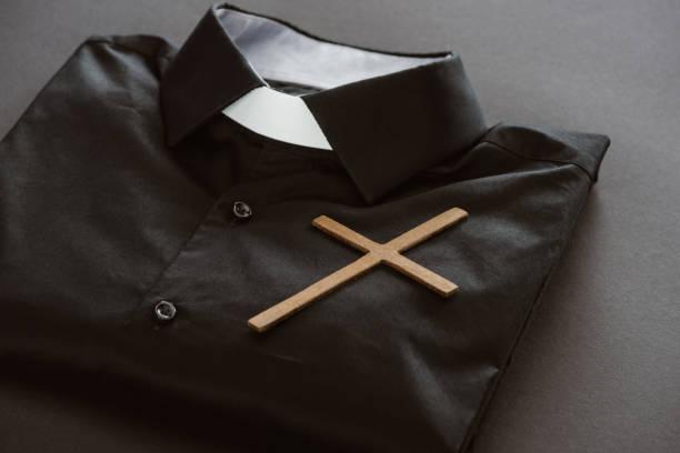 close-up de camisa clerical com cruz na superfície cinza - padre - fotografias e filmes do acervo