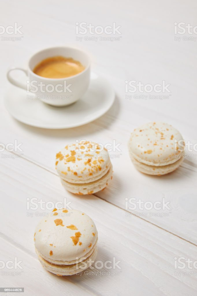 closeup shot of coffee cup and three macarons on white wooden table zbiór zdjęć royalty-free
