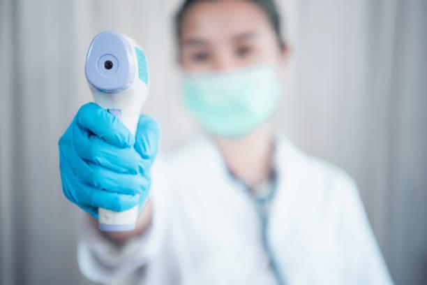 적외선 이마 온도계를 사용하여 바이러스 증상의 체온을 확인하기 위해 준비 된 보호 수술 마스크를 착용한 의사의 클로즈업 샷 - 온도 뉴스 사진 이미지