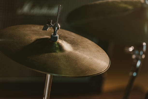 close-up shot of drum cymbal under spotlight on stage close-up shot of drum cymbal under spotlight on stage cymbal stock pictures, royalty-free photos & images