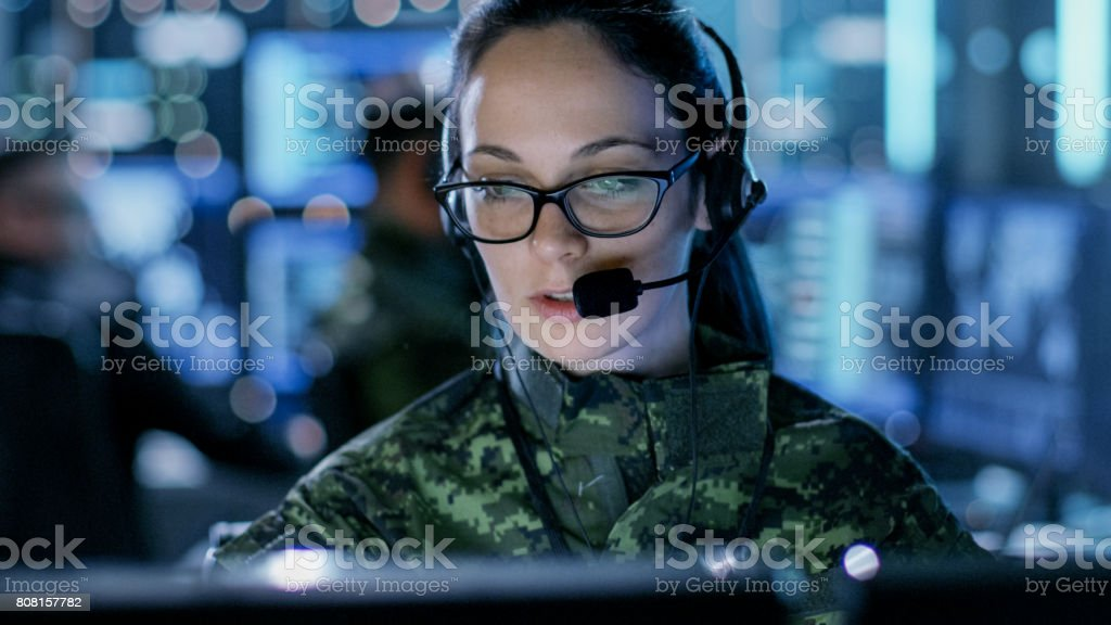 Close-up shot of Female Army Officer Using Computer in Headphones. In the Background Busy System Control Center with People Working, Displays with Information. stock photo