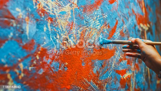 Close-up Shot of Female Artist Hand, Holding Paint Brush and Drawing Painting with Red Paint. Colorful, Emotional Oil Painting. Contemporary Painter Creating Modern Abstract Piece of Fine Art