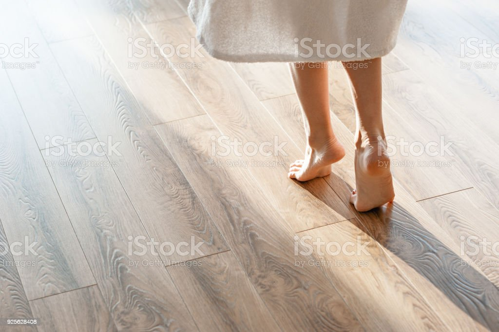Closeup shot of female feet under bed at morning Closeup shot of female feet under bed at morning. Adult Stock Photo