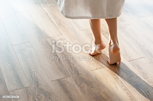 istock Closeup shot of female feet under bed at morning 925628408