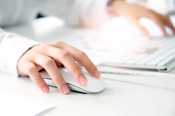 nahaufnahme von weiblichen hand halten maus und arbeiten mit desktop-computer. - computermaus stock-fotos und bilder