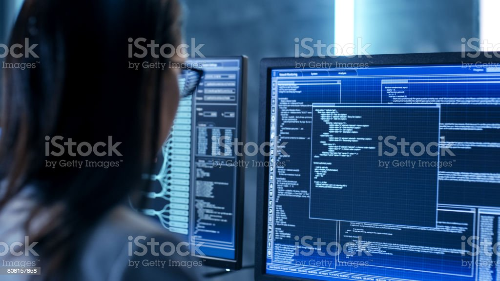 Close-up Shot of Female IT Engineer Working in Monitoring Room. She Works with Multiple Displays. stock photo
