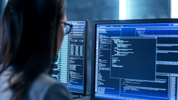 close-up shot of female it engineer working in monitoring room. she works with multiple displays. - female spy stock photos and pictures