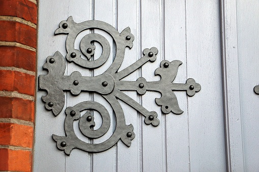 Closeup shot of forged hinge on a wooden wall