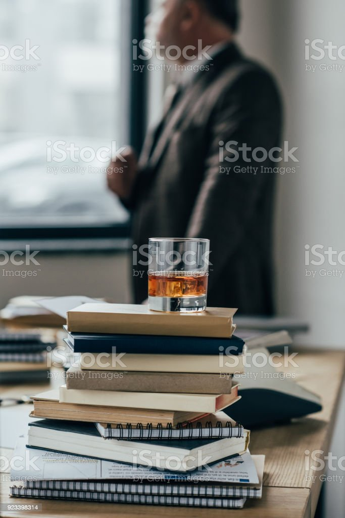 close-up shot of glass of whiskey on stack of books with senior man standing blurred on background stock photo