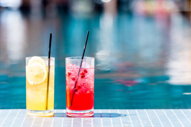 close-up shot of glasses of delicious red and orange cocktails on poolside close-up shot of glasses of delicious red and orange cocktails on poolside poolside stock pictures, royalty-free photos & images