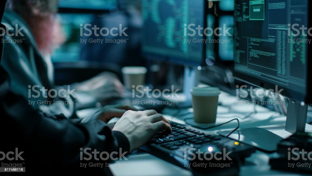 Close-up Shot of Hacker using Keyboard. There is Coffee Cups and Computer Monitors with Various Information. stock photo