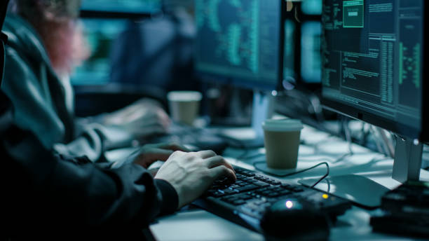 close-up shot of hacker using keyboard. there is coffee cups and computer monitors with various information. - hacker stock photos and pictures