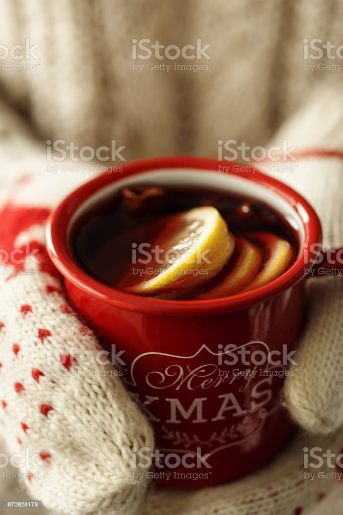 Closeup shot of hands in knitted gloves holding red mug with hot...