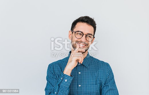 951331990 istock photo Closeup shot of handsome Caucasian entrepreneur in glasses and blue shirt, looking away with happy smile showing white teeth, holding his chin. People, business and success concept.Advertisement space 951331584