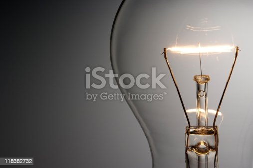 Close-up shot of illuminated light bulb in front of gradation background with copy space.