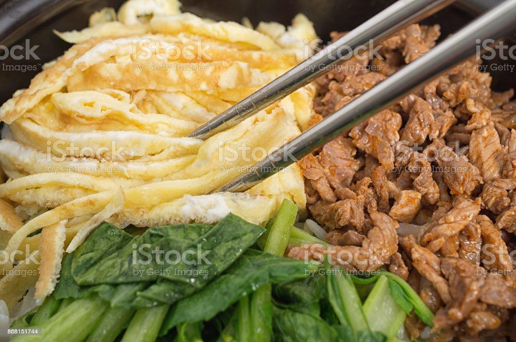 Closeup shot of Korean bibimbap dish with metallic chopsticks stock photo