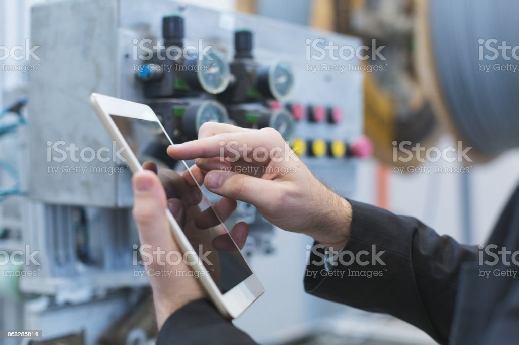 Closeup shot of male hands using tablet pc at factory stock photo