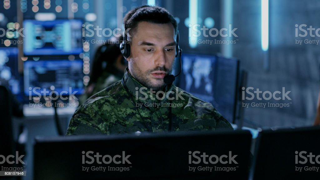 Close-up shot of Military Technical Support Professional Gives Instructions Using Headset. He's in a Monitoring Room with Other Officers and Many Working Displays in Background. stock photo
