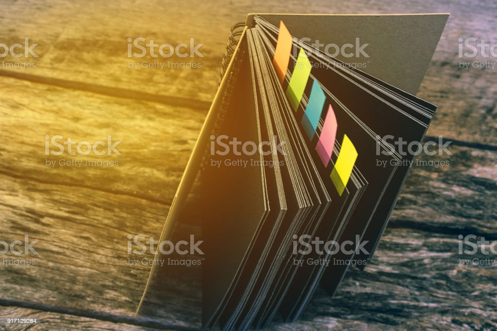 Closeup shot of notebook with color note tab. Notebook with colors note tab on wooden table background,  for design or add text message. Education concept. stock photo
