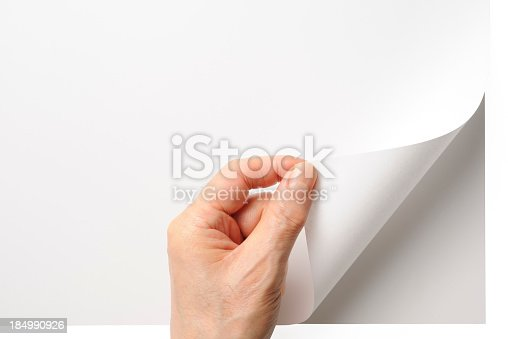 Close-up shot of a hand turning a blank page isolated on white background with clipping path.