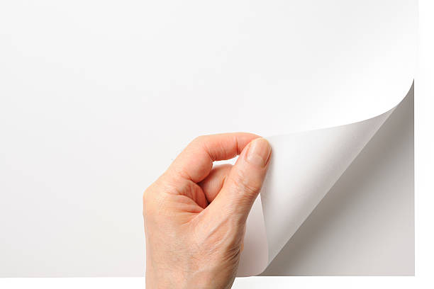 close-up shot of opening a blank page by the hand - page stock pictures, royalty-free photos & images